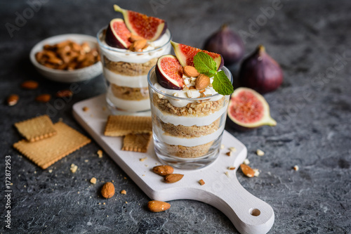 Tuinposter Dessert Layered mascarpone dessert with crushed vanilla biscuits, figs and almonds