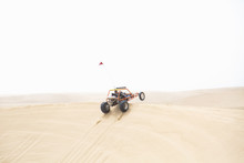 A Sand Rail Catching Air As It Jumps A Sand Dune