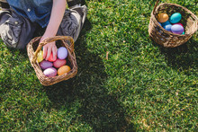 Child Kneeling In Grass With Easter Eggs