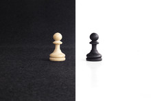 Pair Of Peon Chess Peaces Confronted As Opposites In Black And White Background