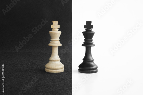 Fotografering  Pair of king chess peaces confronted as opposites in black and white background