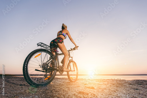 Fotobehang Fiets A strong blonde woman in a multicolored suit sits on a bicycle in a desert area near the water and looks at the sun. Fitness concept. Back view