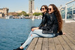 Two young girlfriends sitting on wooden pier