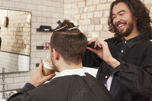 Barber cutting client's hair. Poster