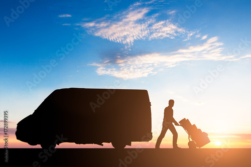 Fotografía  Silhouette Of Delivery Courier With Cardboard Boxes On Trolley