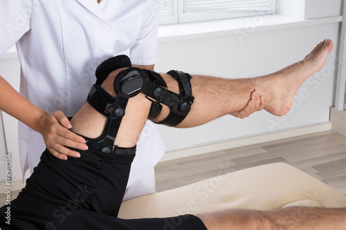 Fotografiet  Physiotherapist Fixing Knee Braces On Man's Leg