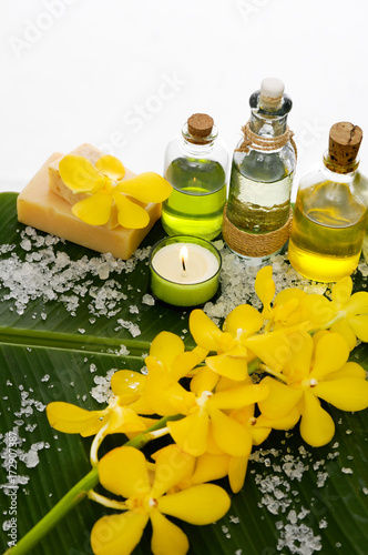 Deurstickers Spa Spa setting on banana leaf with yellow orchid ,candle, salt in spoon