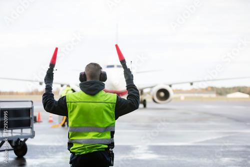 Fotografie, Obraz  Ground Crew Signaling To Airplane