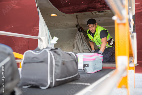 Photographie Worker Placing Baggage On Conveyor To Unload Airplane