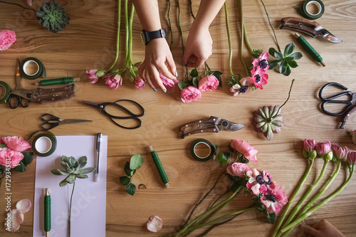 Poster Fleur workshop florist. The hand of the girl on the background of the table with flowers. Create floral arrangements.