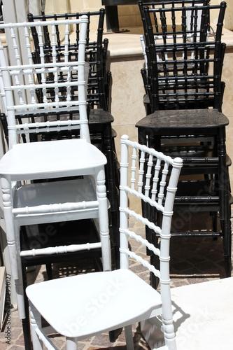 Fototapeta Lager: Gestapelte Stühle aus Holz auf der Terrasse eines Restaurants