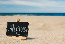 """A Small Wooden Malbert With A Slate On Which Chalk Is Written """"august"""". The Concept Of Summer Month, Calendar. Beach, Golden Sand, Blue Baltic Sea, Blue Sky."""