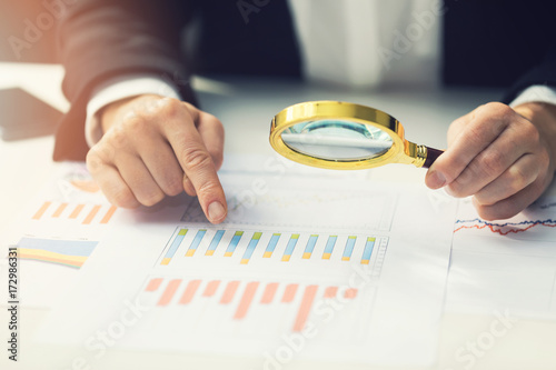 Photo business women using magnifying glass to review financial summary chart report