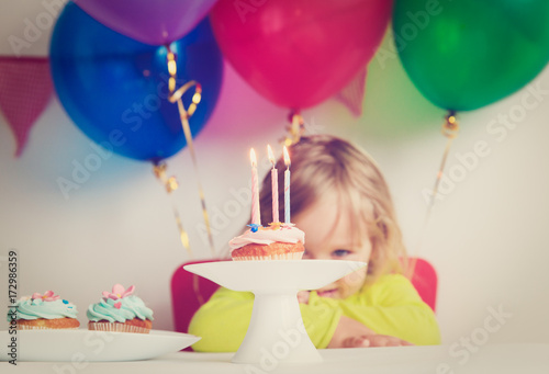 little girl making wish at birthday party Poster