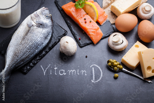 Fototapeta Black slate table with product rich in vitamin D and omega 3. Written word vitamin D by white chalk. obraz