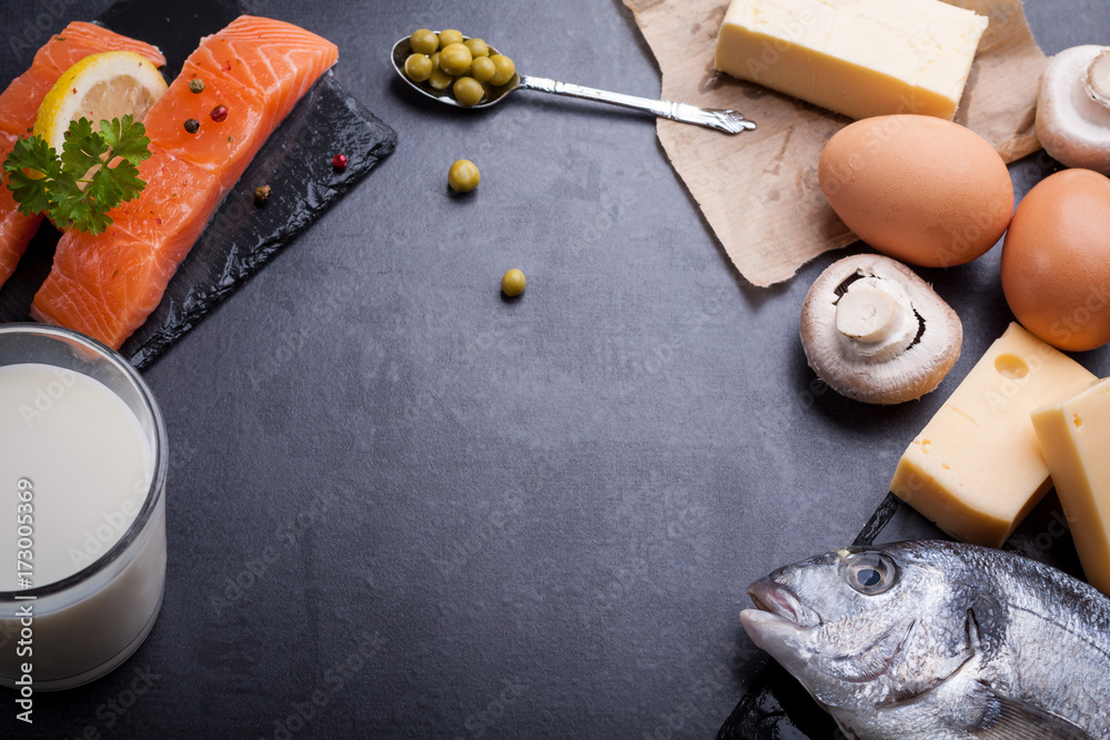 Fototapeta Black table with ingredients of food rich in vitamin D and omega 3, with copy space.