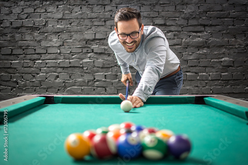 happy-businessman-playing-a-game-of-billiards-and-preparing-to-break-pyramid-of-balls-on-the-table