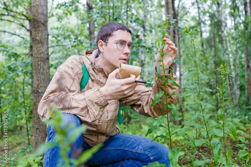 Image of man with notebook and pencil studying plant Fototapet