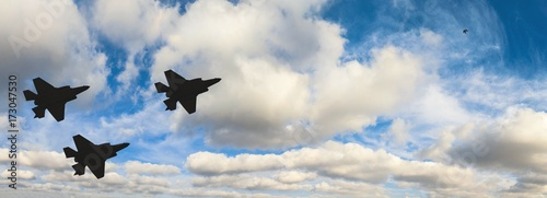 obraz dibond Silhouettes of three F-35 aircraft against the blue sky and white clouds