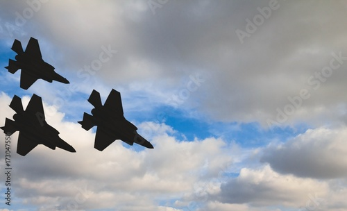 Fotografía Silhouettes of three F-35 aircraft against the blue sky and white clouds
