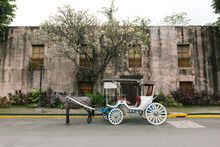 A White Horse-drawn Carriage Parked In Front Of A Spanish Colonial Period Wall With Wooden Windows