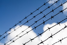 Black Barbed Wires Over Cloudy Blue Sky