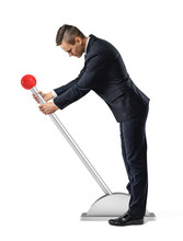 A Businessman Stands At A Large Lever With A Red Round Knob And Starts To Move It.