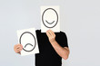 Man holding two cards with happy and unhappy faces drawn representing different options. Duality concept.