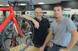 portrait of positive men posing in bicycle store