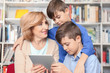 Teacher and children with tablet at school library
