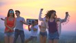 The young people with a boom box dancing on the sunset background