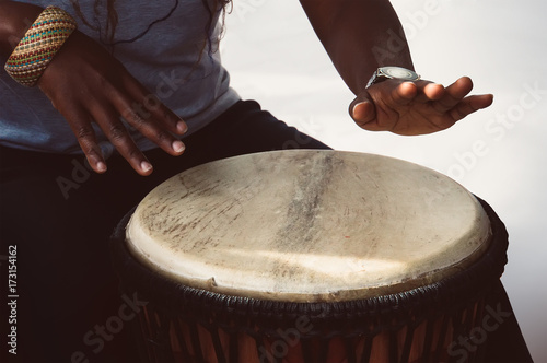 A female african musician plays the djembe drum. Wallpaper Mural