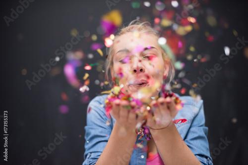 Obraz woman blowing confetti in the air - fototapety do salonu