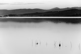 A lake at dusk, with soft light, distant hills and mountains, fishing nets in the foreground an a lot of empty space - 173174771