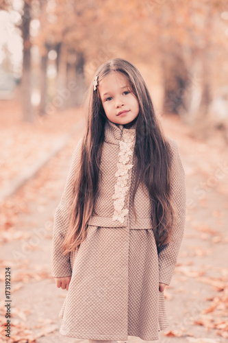 9142416da Pretty kid girl 4-5 year old with long hair wearing stylish coat posing  over autumn background. Looking at camera. Childhood.