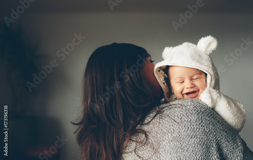 Cute little boy smiling in his mother's arms Canvas Print
