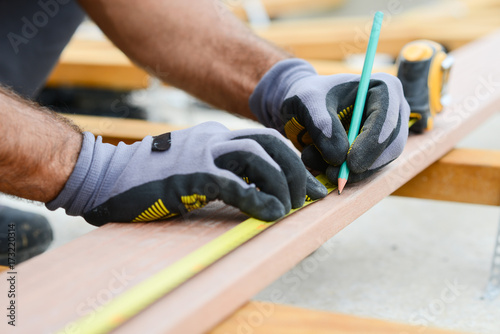 Obraz close up detail of manual worker hands working with a measuring tape and pencil in wood plank - fototapety do salonu