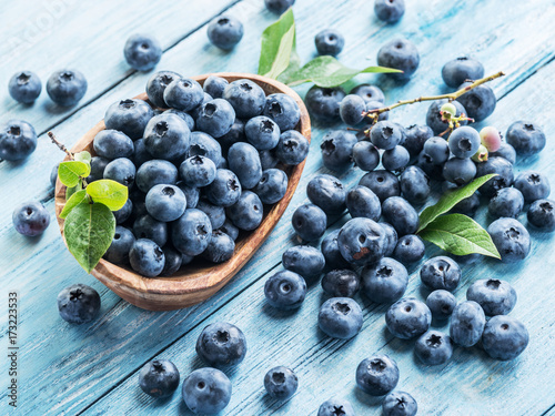 Blueberries in the wooden bowl on the table.