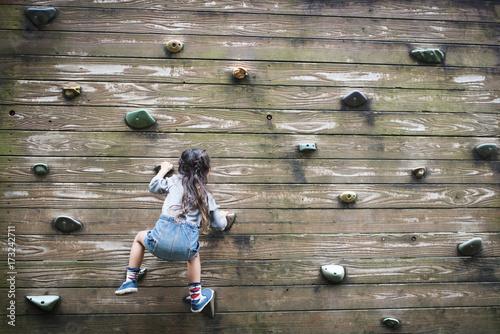 Little girl climbing the wall Wallpaper Mural