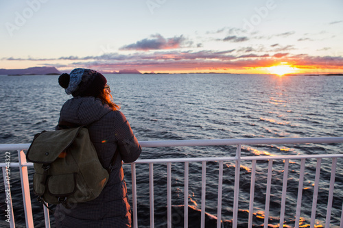 Fotografía  Woman traveler with backpack on the deck of a ferry in the Atlantic Ocean