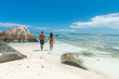 Back view of happy couple walking on Seychelles beach