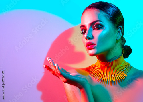Foto op Plexiglas Beauty Fashion model woman in colorful bright lights posing in studio. Portrait of beautiful sexy girl with trendy makeup and manicure