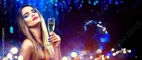 Fotografie, Obraz  Sexy model girl drinking champagne over holiday glowing background