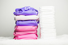 Stacks Of Eco Friendly Washable Textile Diapers And Modern Disposable Diapers Together.