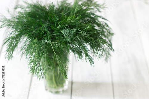 Leinwand Poster Fresh dill in a glass on a white wooden background