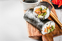 Trend Hybrid Food. Japanese, Asian Cuisine. Sushi-burrito, Sandwich With Salmon, Hayashi Wakame, Daikon, Pickled Ginger, Red Caviar. On A White Marble Table, With Chopsticks And Soy Sauce. Copy Space