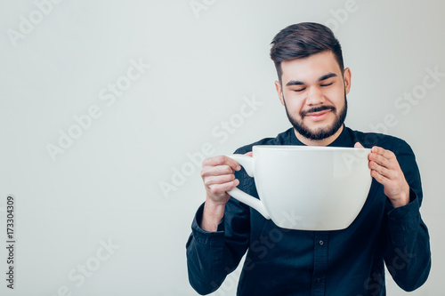 Fotografiet business man holding a funny huge and oversized cup of black coffee in caffeine