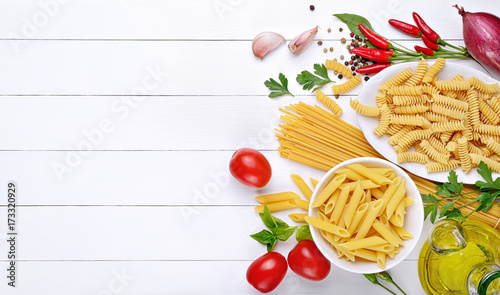 Pasta and ingredients: spaghetti, pens and fusilli, tomatoes, chili peppers, garlic, parsley, basil and extra virgin olive oil