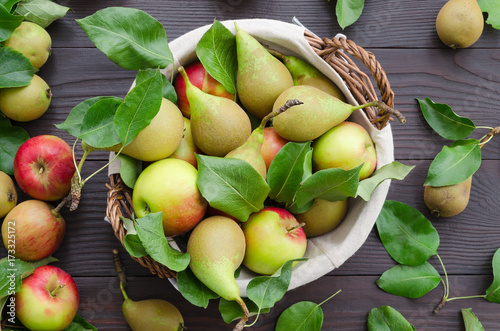Basket with apples and pears on dark wooden background