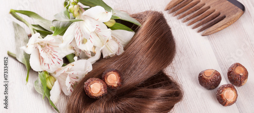 Fragment of healthy shiny woman hair and natural products for haircare